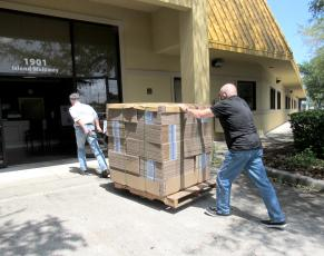 Nassau County Council on Aging Transportation Director Mike Hays and volunteer Philip Chapman roll a pallet of WestRock-donated boxes into the Fernandina Beach Life Center.