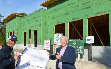 Crawford Jewelers owner Gary Crawford, right, holds up construction plans of The Palms, a 4,200-square-foot shopping center being constructed on Sadler Road. Holding up the plans are Steve Johnson with Johnson Home Builders of Fernandina Beach. JOHN SCHAFFNER/FOR THE NEWS-LEADER