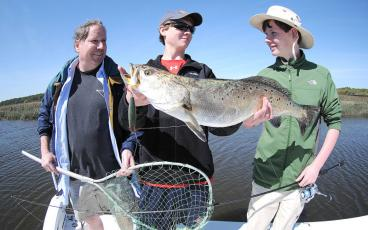 George Holstrom, Josh Holstrom and Will Blankenship, from left, are pictured with a giant Amelia Island sea trout caught with a minnow-type plug. TERRY LACOSS/SPECIAL