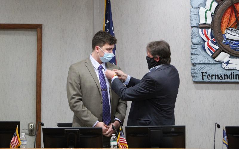 Outgoing Mayor Johnny Miller gives the pin he wore to his last City Commission on Tuesday to Bradley Bean, who won Miller's Group 1 seat. Miller was term-limited from running again. JULIA ROBERTS/NEWS-LEADER