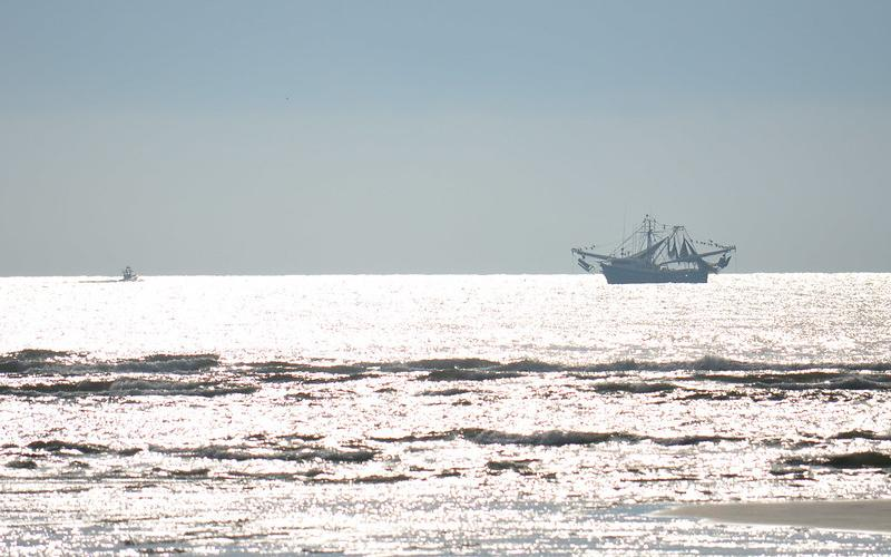A recreational fishing boat shares the ocean with a commercial shrimp boat.  Florida Fish & Wildlife Conservation Commission