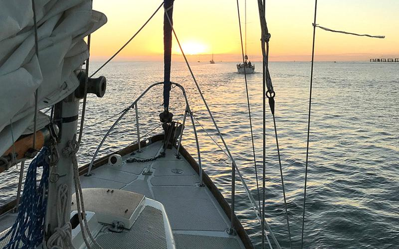 Aboard sailing vessel Wayward Wind heading out of the St. Simons channel to the starting line at sunrise behind a row of competitor boats. SUBMITTED