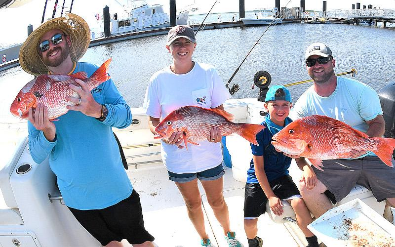 William Boyle, Julie, Breck and William Benton with a nice catch of red snapper, left. Capt. Bryce Schmidt cleans a nice catch of red snapper, right. TERRY LACOSS/SPECIAL