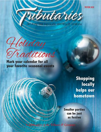 "Cover of the Winter 2020 ""Winter Traditions"" Edition of Tributaries magazine; image is of blue and silver christmas bulb ornaments on a blue background"